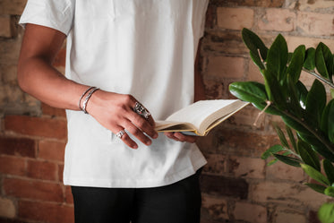 person stands by a brick wall and holds a book open