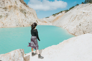 person stands by a still lake of blue water