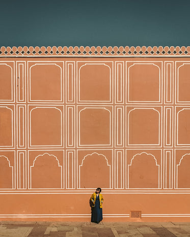 person stands by tall orange wall and looks up