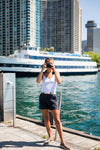person stands by waterfront and holds camera up to take a picture