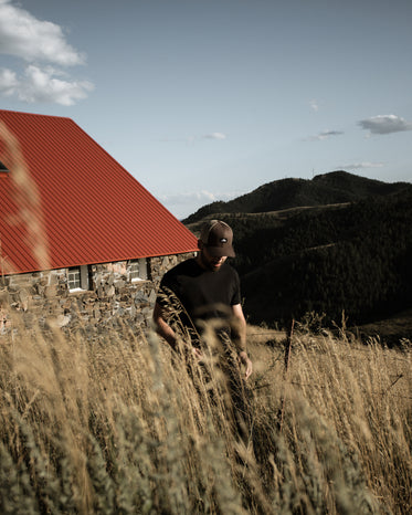 person stands in golden wheat with a building behind