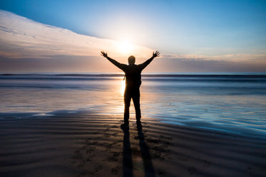 person stands on a beach with their arms out at sunset