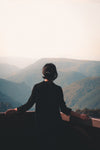 person stands on look out at a hazy mountain view