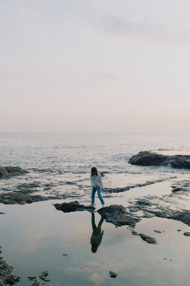 person stands on rocks poking out of the ocean shoreline