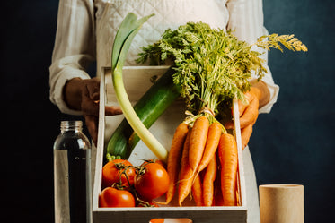 person tilts a box full of vegetables towards the camera