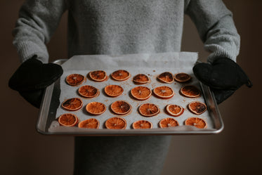 person tilts silver tray filled with baked oranges forward