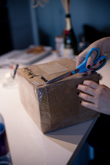 person uses scissors to cut open a taped cardboard box