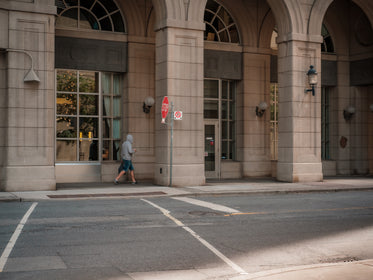 person walking under a city building with tall archways