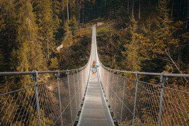 person walks to the otherside of a metal suspension bridge