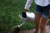 person waters plants with a watering can