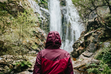 person wearing a raincoat looks at tall waterfall