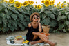 person wearing sunglasses enjoys a picnic by a sunflower field