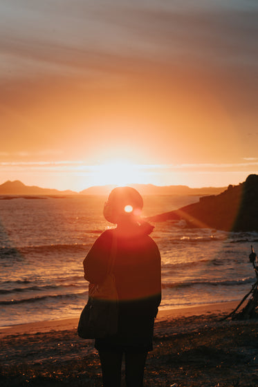 person wears a facemask and takes in a beautiful sunset