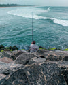 person with fishing rod of mossy green rocks