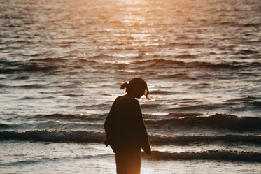 person with long hair silhouetted at sunset by the water