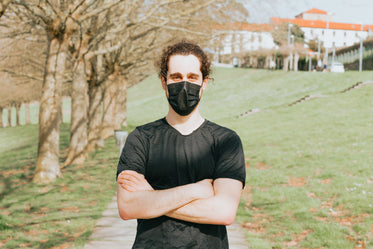 person with their arms crossed and wearing a facemask