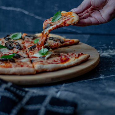 persons hand lifts a slice of pizza from round plate