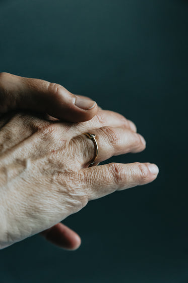 persons hand with a ring on it against blue