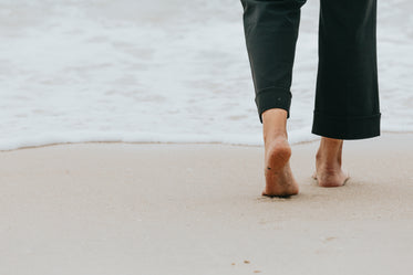 persons legs walking towards the water on a beach