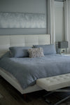 photo of a bed with a white bed frame and blue sheets
