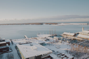 photo of snow covered buildings by a harbour
