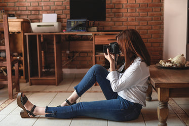 photographer sits on floor holding a camera to their face