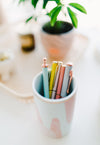 pink cup full of pens
