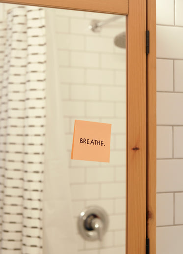 pink note reads breath on a bathroom mirror