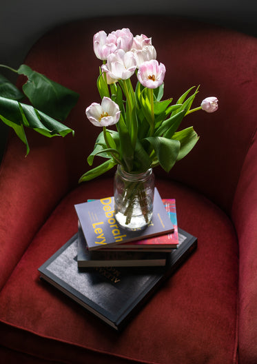 pink tulips on a glass jar on top of a stack of books