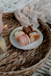 plate of macarons on a wicker tray