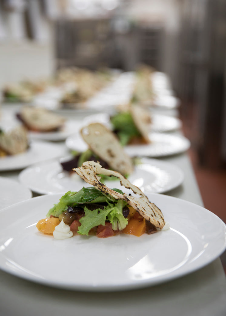 Plates Being Prepared For Service In A Restaurant Kitchen
