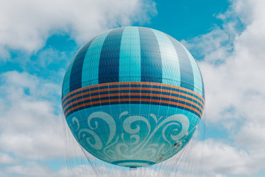 playful patterned sphere hot air balloon floats in blue sky