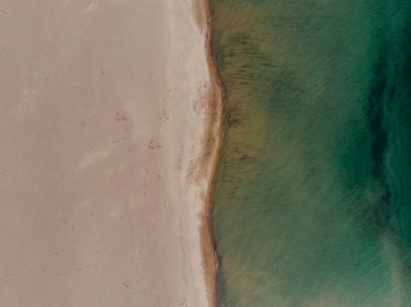 portrait image of contrast between sand and sea