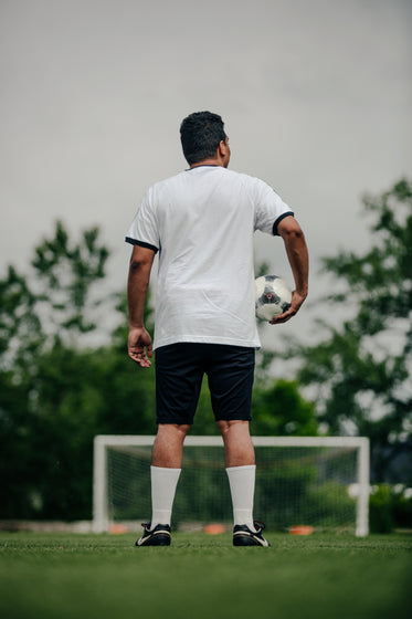 portrait of soccer player holding ball on empty field