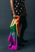 portrait of tattoos bracelets and rings holding pride flag