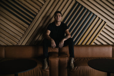 portrait of young man against large geometric wood wall