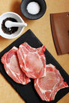 prepping and seasoning raw pork chops with slate and cleaver