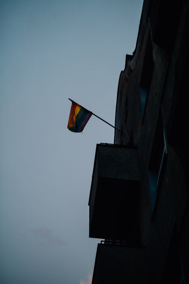 pride flag hangs on a building at sunset