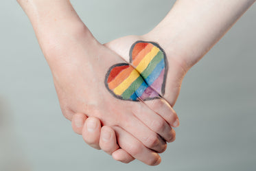 pride heart on two holding hands