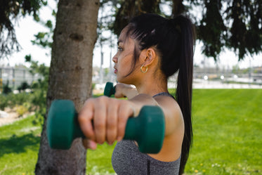 profile of a woman who is holding hand weights outdoors