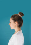 profile of a woman with her hair in a scrunchie bun