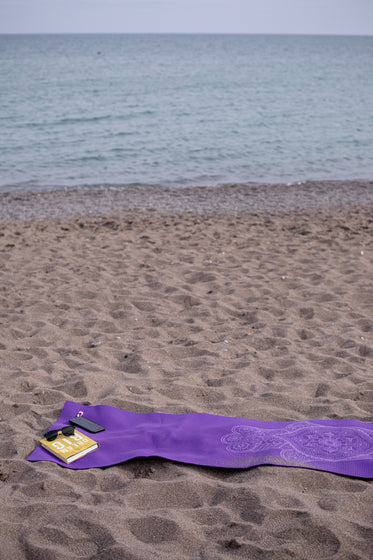 purple towel on a beach with book and cellphone