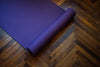 purple yoga mat partially rolled on a wooden floor