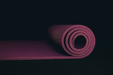 purple yoga mat partially rolled on black