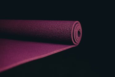 purple yoga mat partially rolled up on black