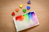 rainbow painted wooden hearts beside watercolour canvas