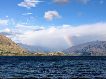 rainbow reaches for clouds by shore