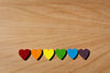 rainbow wooden hearts lined up on oak table