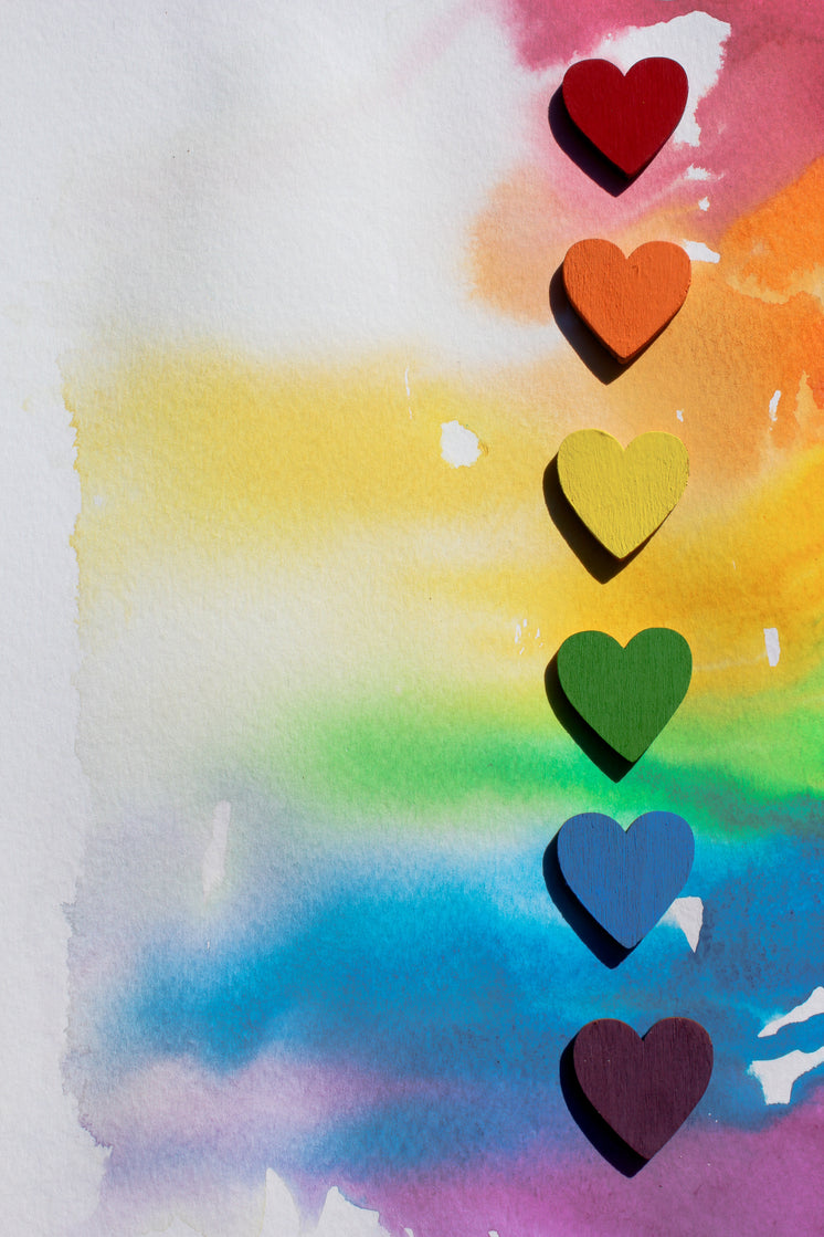 Rainbow Wooden Hearts Lined Up On Watercolour Canvas