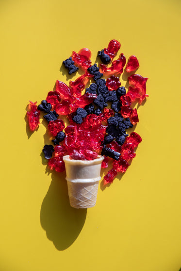 red and black gummies spill out of an icecream cone